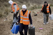 Working unpaid on a Community Payback scheme. Young offenders clean up the beach, picking up and removing rubbish using litter pickers, Freshwater West, Pembrokeshire, Wales. - Paul Box - 16-02-2011