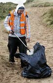 Working unpaid on a Community Payback scheme. Young offenders clean up the beach, picking up and removing rubbish, Freshwater West, Pembrokeshire, Wales. - Paul Box - 16-02-2011