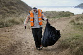 Working unpaid on a Community Payback scheme. Young offenders clean up the beach, picking up and removing rubbish using litter pickers, Freshwater West, Pembrokeshire, Wales. - Paul Box - ,2010s,2011,bag,bags,beach,BEACHES,bin bag,bin bags,binbag,binbags,black,clean up,cleanup,clearing,clJ,COAST,coastal,coasts,communities,Community,community service,crime,criminal,Criminal Justice Syst