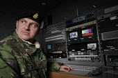 Army Cameraman sergeant Hennessey in the film editing van. The1st Battalion The Black Watch (Royal Highland Regiment) arriving back to their base, Battlesbury Barracks, Warminster 2004. The troops had... - Paul Box - audiovisual production specialist,2000s,2004,army,ARRIVAL,arrivals,arrive,arrived,arrives,arriving,beret,blackwatch,camera operator,Cameraman,camouflage,closed,closing,closure,closures,conflict,edit,e