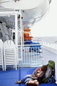A backpacker sleeping on deck onboard The Armorique ferry crossing to Roscoff in France. - Paul Box - 2010s,2011,asleep,backpack,backpacker,backpackers,backpacking,bag,bags,boat,boats,Brittany,cargo,chair,chairs,cross,crosses,crossing,crossings,deck,decks,EBF,Economic,Economy,English Channel,EXHAUSTED