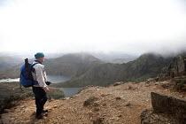 A man climbing Grib Goch ridge in Snowdonia National Park, North Wales. Lyn Llydaw below. - Paul Box - 2010s,2011,age,ageing population,arête,climb,climbing,country,countryside,elderly,eni,environment,Environmental Issues,hobbies,hobby,hobbyist,holiday,holiday maker,holiday makers,holidaymaker,holiday