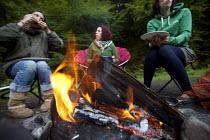 Women eating food around a campfire at Pool Farm Campsite, Porlock, Somerset. - Paul Box - 09-08-2011
