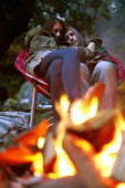 A couple cuddling next to a fire at Pool Farm Campsite, Porlock, Somerset. - Paul Box - ,2010s,2011,adult,adults,campfire,camping,campsite,campsites,chair,chairs,couple,COUPLES,cuddle,cuddling,embrace,EMBRACING,Farm,FEMALE,fire,fires,Firewood,holiday,holiday maker,holiday makers,holidaym