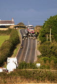 Fire engines, lorries and a motorcycle being held up as cows are crossing the road, Pembrokeshire, Wales. - Paul Box - 2000s,2009,agricultural,agriculture,animal,animals,bike,bikes,capitalism,capitalist,cattle,CONGESTED,congestion,country,countryside,cow,cows,cross,crosses,crossing,domesticated ungulate,domesticated u