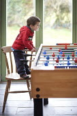 A boy playing table football at a holiday home, Pembrokeshire, Wales. - Paul Box - 08-02-2011