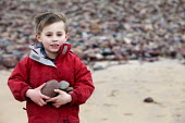 A boy collecting pebbles, Freshwater West, Pembrokeshire, Wales. - Paul Box - 2010s,2011,beach,BEACHES,boy,boys,child,CHILDHOOD,children,COAST,coastal,coasts,collecting,eni,environment,Environmental Issues,holiday,holiday maker,holiday makers,holidaymaker,holidaymakers,holidays