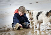 A girl playing with mud and a dog, Freshwater West, Pembrokeshire, Wales. - Paul Box - 2010s,2011,animal,animals,beach,beaches,child,CHILDHOOD,children,COAST,coastal,coasts,dog,dogs,EARLY YEARS,female,females,girl,girls,holiday,holiday maker,holiday makers,holidaymaker,holidaymakers,hol