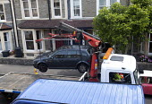 A car being removed to allow contractors to replace a leaking water pipe and install a water meter. Bristol. - Paul Box - 27-06-2011