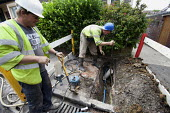 Contractors in a hole in the ground, replacing a leaking water pipe and installing a water meter. Bristol. - Paul Box - 27-06-2011