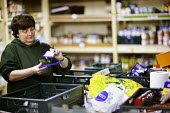 A volunteer in the warehouse sorts donated food at the Cardiff Foodbank a franchise of the Trussell Trust and a part of the National Foodbank Network. It is a project to help and support those sufferi... - Paul Box - 10-05-2012