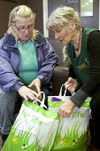 A volunteer gives some bags of food to a Foodbank user at the City Foodbank Centre. Cardiff Foodbank is part of the Trussell Trust and the National Foodbank Network. It is set up to help and support t... - Paul Box - 10-05-2012