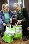 A volunteer gives some bags of food to a Foodbank user at the City Foodbank Centre. Cardiff Foodbank is part of the Trussell Trust and the National Foodbank Network. It is set up to help and support t... - Paul Box - &,2010s,2012,agencies,agency,aid,assistance,BAG,bags,belief,charitable,charities,charity,christian,christianity,christians,cities,city,communicating,communication,conversation,conversations,conviction