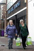 A volunteer gives some bags of food to a Foodbank user at the City Foodbank Centre. Cardiff Foodbank is part of the Trussell Trust and the National Foodbank Network. It is set up to help and support t... - Paul Box - &,2010s,2012,agencies,agency,aid,assistance,BAG,bags,belief,charitable,charities,charity,christian,christianity,christians,cities,city,conviction,distribution,donations,EQUALITY,excluded,exclusion,fai