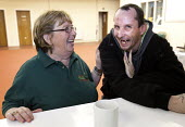 A volunteer has a laugh with a Foodbank user at the City Foodbank Centre. Cardiff Foodbank is part of the Trussell Trust and the National Foodbank Network. It is set up to help and support those suffe... - Paul Box - &,2010s,2012,agencies,agency,aid,assistance,belief,charitable,charities,charity,christian,christianity,christians,cities,city,communicating,communication,confiding,conversation,conversations,convictio