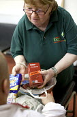 A volunteer gives some bags of food to a Foodbank user at the Ely Foodbank Centre. Cardiff Foodbank is part of the Trussell Trust and the National Foodbank Network. It is set up to help and support th... - Paul Box - &,2010s,2012,agencies,agency,aid,assistance,BAG,bags,belief,charitable,charities,charity,christian,christianity,christians,cities,city,conviction,distribution,donations,EQUALITY,excluded,exclusion,fai