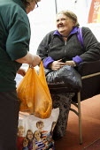 A volunteer gives some bags of food to a Foodbank user at the Ely Foodbank Centre. Cardiff Foodbank is part of the Trussell Trust and the National Foodbank Network. It is set up to help and support th... - Paul Box - &,2010s,2012,age,ageing population,agencies,agency,aid,assistance,BAG,bags,belief,charitable,charities,charity,christian,christianity,christians,cities,city,communicating,communication,conversation,co