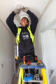 An electrician installing a smoke alarm in new housing near Taunton, Somerset. - Paul Box - 22-03-2012