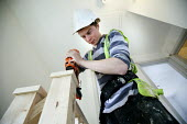 A carpenter fitting a bannister, new housing near Taunton, Somerset. - Paul Box - 2010s,2012,apprentice,apprentices,apprenticeship,apprenticeships,build,builder,builders,building,building site,Building Worker,BUILDINGS,carpenter,carpenters,chippy,construction,Construction Industry,