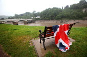 A soggy Union Jack flag overlooking the river Wye that separates Wales and England, at the celebrations of the Queens Diamond Jubilee, Chepstow, Wales. - Paul Box - 2010s,2012,bench,border,bridge,CELEBRATE,celebrating,celebration,celebrations,CLIMATE,conditions,english,flag,flags,holiday,holiday maker,holiday makers,holidaymaker,holidaymakers,holidays,Leisure,LFL