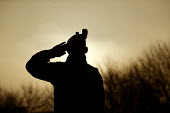 A soldier salutes at sunrise. The 1st Battalion The Black Watch (Royal Highland Regiment) (1 BW) arrive back to their base on December 11, 2004 at the Battlesbury Barracks, Warminster, England. The tr... - Paul Box - 11-12-2004