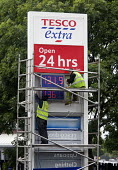 Tesco Extra petrol station. Workers maintaining the price of fuel sign. - Paul Box - 11-06-2012