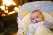A 10 week old baby boy sits in front of a wood fire. Bristol - Paul Box - 16-12-2012