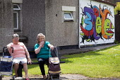 Two ladies have a cigarette on a bench in front of graffiti, Southville, Bristol. - Paul Box - 31-05-2013