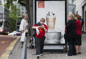 An overweight boy walks past a Mcdonalds advertisement whilst his mother watches him, Bristol - Paul Box - 2010s,2013,adolescence,adolescent,adolescents,adult,adults,advert,ADVERTISED,advertisement,advertisements,advertising,ADVERTISMENT,adverts,Body Weight,bottle,bottles,boy,boys,Bus Stop,child,CHILDHOOD,