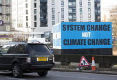 A Range Rover passes a System change not Climate change Billboard, The Bearpit, Bristol, European Green Capital - Paul Box - 2010s,2015,4x4,ACE,activist,activists,AFFLUENCE,AFFLUENT,against,anti,Art Gallery,arts,AUTO,AUTOMOBILE,AUTOMOBILES,AUTOMOTIVE,billboard,billboards,Bourgeoisie,CAMPAIGN,campaigner,campaigners,CAMPAIGNI