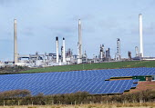 Solar farm being installed in Pembrokeshire in front of the Valero oil refinery, Rhoscrowther, Pembrokeshire. - Paul Box - 2010s,2015,capitalism,capitalist,Chevron Oil Refinery,chimney,chimneys,country,countryside,EBF,Economic,Economy,ELECTRICAL,electricity,energy,farm,farmed,farmland,farms,generator,Industries,industry,m