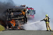Firefighters extinguish a fire after The Pembrokeshire Coastal Cruiser tourist passenger bus burst into flames, Freshwater West, Wales - Paul Box - ,2010s,2015,accident,accidental,accidents,adult,adults,bus,bus service,buses,Cruiser,destroyed,destruction,DIA,employee,employees,Employment,fire,Fire and Rescue,fire brigade,Fire Engine,Firefighter,f