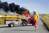 The Pembrokeshire Coastal Cruiser tourist passenger bus bursting into flames, Freshwater West, Wales. A lifeguard blocks the road. - Paul Box - ,2010s,2015,accident,accidental,accidents,bus,bus service,buses,communicating,communication,Cruiser,destroyed,destruction,DIA,employee,employees,Employment,fire,fires,flame,flames,highway,incident,inc