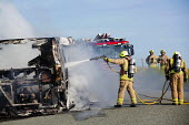 Firefighters extinguish a fire after The Pembrokeshire Coastal Cruiser tourist passenger bus burst into flames, Freshwater West, Wales - Paul Box - 2010s,2015,accident,accidental,accidents,adult,adults,bus,bus service,buses,Cruiser,destroyed,destruction,DIA,employee,employees,Employment,fire,Fire and Rescue,fire brigade,Fire Engine,Firefighter,fi