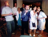 Party goers singing karaoke. - Paul Box - 2000s,2002,alcohol,dr,drink,drinking,enjoying,enjoyment,FEMALE,Fun,getting,Getting Married,hotel,HOTELS,lfl leisure,male,man,marriage,marriages,microphone,parties,Party,people,person,persons,reception