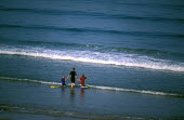A mother takes her children paddling , Woolacombe , North Devon - Paul Box - 2000s,2003,active,adult,adults,beach,BEACHES,blue,board,bodies,body,child,CHILDHOOD,children,childs,coast,coastal,coasts,country,countryside,DAD,DADDIES,DADDY,DADS,eni environmental issues,EXERCISE,ex