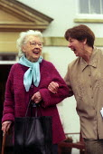 A happy elderly lady outside her retirement home, Bristol with a helper - Paul Box - 01-12-2003
