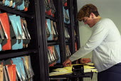 An office worker sorting through files. - Paul Box - 07-12-2003