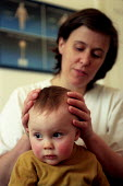A young child visits a chiropractor for a head massage, Bristol - Paul Box - 01-12-2003