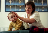 A young child visits a chiropractor for a head massage, Bristol - Paul Box - 2000s,2003,alternative,BABIES,baby,boy,BOYS,CARE,carer,carers,child,Child Care,childcare,childhood,CHILDMINDING,children,chiropractic,cities,city,complementa,Cranial,Cranium,EARLY YEARS,EMOTION,EMOTIO
