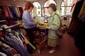 Charity shop, an old lady shops. - Paul Box - 2000s,2003,2nd,adult,adults,age,ageing population,apparel,basket,bought,buy,buyer,buyers,buying,cancer,CANCERS,charitable,charity,clothes,clothing,commodities,commodity,consumer,consumers,customer,cus