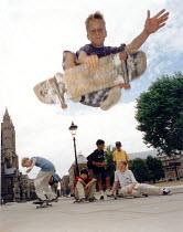 Skateboarder jumping through the air, Bristol. - Paul Box - 2000s,2004,adolescence,adolescent,adolescents,boy,boys,child,CHILDHOOD,children,cities,city,Council Services,Council Services,enjoying,enjoyment,EXTREME,fun,having,hobbies,hobby,hobbyist,jumping,juven