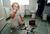Girl playing with makeup in the bathroom at home. - Paul Box - 26-01-2004