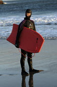 A woman with body boarding in Wales - Paul Box - 2000s,2004,activity,balaclava,beach,BEACHES,boarding,bodies,body,COAST,coastal,coasts,cold,day,EMOTION,EMOTIONAL,EMOTIONS,Extreme Sports,female,females,fewmale,flippers,gear,girl,GIRLS,hobbies,hobby,h