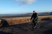 An elderly man cycles on the sea front, Minehead. - Paul Box - 11-01-2004