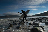 A surfer walks over rocks to go surfing - Paul Box - 2000s,2004,beach,beaches,board,boards,careful,cautious,cautiously,coast,coastal,coasts,dramatic,Extreme Sports,flexible,holiday,holiday maker,holiday makers,holidaymaker,holidaymakers,holidays,LFL Lif