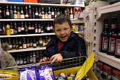 A child sits in corner shop whilst single mother works behind the counter. - Paul Box - 20-01-2004