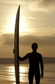 A surfer silhouetted against the setting sun , at Woolacombe Devon - Paul Box - ,2000s,2004,against,beach,beaches,board,boards,COAST,coastal,coasts,hobbies,hobby,hobbyist,holiday,holiday maker,holiday makers,holidaymaker,holidaymakers,holidays,LFL leisure,long,OCEAN,people,person