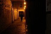 A person walks down a dark alley in Bristol - Paul Box - 2000s,2003,alley,Anxiety,anxious,ANXIOUSNESS,APPREHENSIVE,cities,city,clJ crime,cobbled street,dangerous,dark,fear,fearful,frightening,lamp,lamps,life,ligh,light,lighting,lights,lonely,place,scene,sce