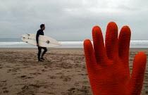 A surfer walks along the beach before going surfing with rubbish on beach. - Paul Box - 2000s,2004,beach,beaches,board,boards,COAST,coastal,coasts,eni,environment,Environmental Issues,glove,gloves,hand,hands,holiday,holiday maker,holiday makers,holidaymaker,holidaymakers,holidays,LFL Lif